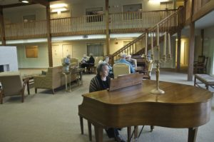 Senior playing the piano and enjoying the lifestyle at Arbor Court